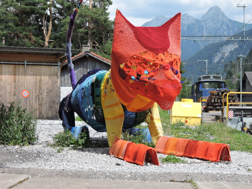 Meet the Fiber Arts Cat of Rossinière's Train Station, A Colorful Yarn Bomb In Switzerland