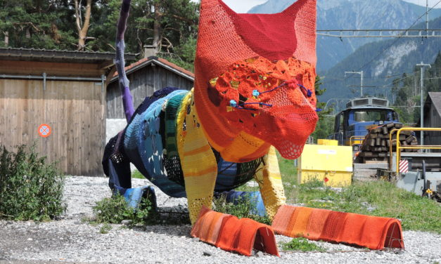 Meet the Fiber Arts Cat of Rossinière's Train Station, A Colroful Yarn Bomb In Switzerland