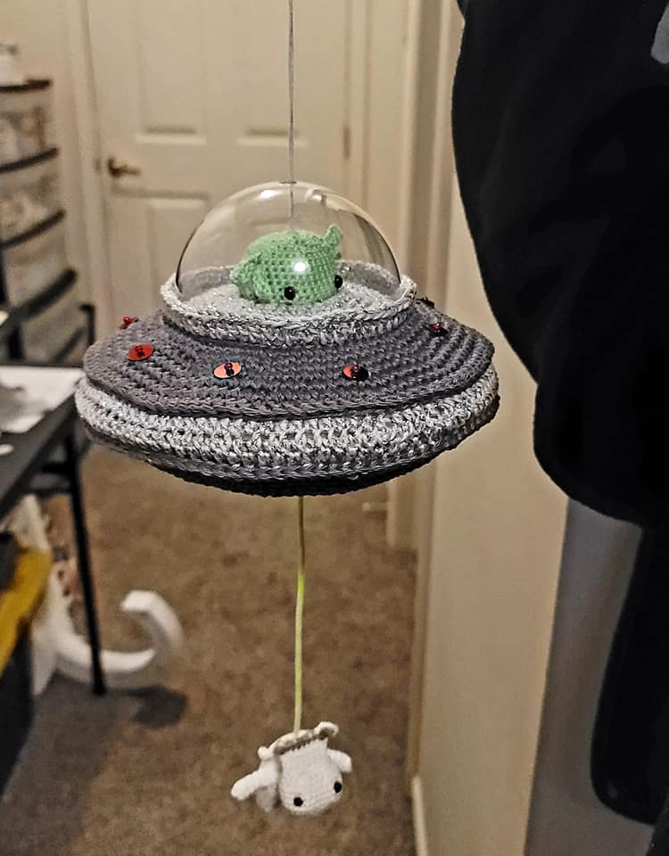 This Crochet Kit Flying Saucer Kit Features an Alien and a Cow and It's a Wind-Up Music Box!